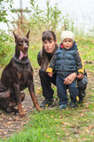 Young woman with her son and doberman dog on walk in autumn park Stock Photos
