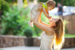 Young woman and her son having fun outdoors. Royalty Free Stock Image