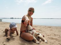 The young woman with her son and puppy on the beach Royalty Free Stock Photos