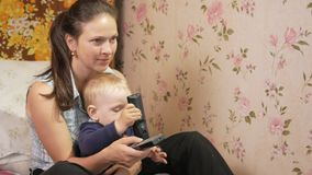 Young woman with her son sitting at home on the couch with remote control from the TV. Look at the screen attentively stock video footage