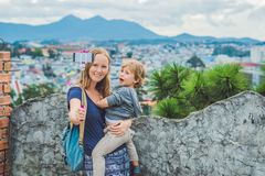 Young woman and her son taking smart phone self portrait picture. Young women and her son taking smart phone self portrait pictures with selfie stickon the Stock Images
