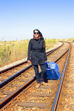 Young woman with her suitcase on a railroad track Royalty Free Stock Photo