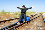 Young woman with her suitcase on a railroad track Stock Photo