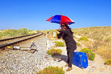 Young woman with her suitcase waiting at a railroad track Royalty Free Stock Photos