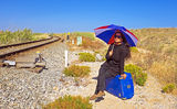 Young woman with her suitcase waiting at a railroad track Royalty Free Stock Images