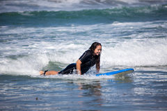 Young woman on her surfboard Stock Image