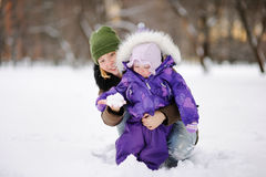 Young woman with her toddler daughter playing with snow Stock Photos