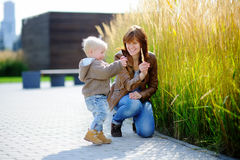 Young woman and her toddler son playing outdoors Stock Photo