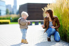 Young woman and her toddler son playing outdoors Royalty Free Stock Image