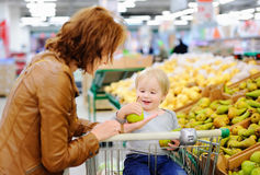 Young woman and her toddler son in a supermarket Royalty Free Stock Images