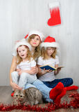 Young woman with her two daughters reading a book Stock Image