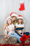 Young woman with her two daughters reading a book Royalty Free Stock Photography