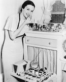 Young woman at her vanity applying lipstick. (All persons depicted are no longer living and no estate exists. Supplier grants that there will be no model Royalty Free Stock Photos