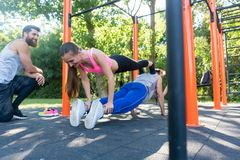 Young woman and her workout partner doing couple push-up exercise royalty free stock photo