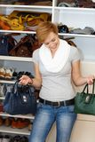 Young woman hesitating among bags Stock Photo
