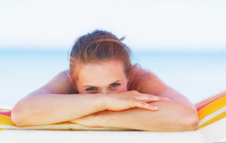 Young woman hide behind hands while laying on chaise-longue Royalty Free Stock Photos