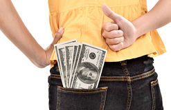 Young woman hide lots of dollars and showing thumb up Stock Photos
