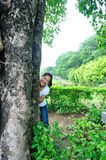 Young woman smile behind lime tree Royalty Free Stock Images