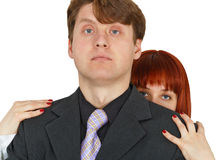 Young woman hides behind big shoulders of man Stock Photo