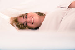 Young woman hiding in Bed under the sheets Royalty Free Stock Photography