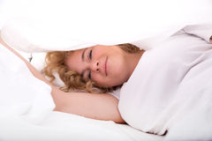 Young woman hiding in Bed under the sheets Royalty Free Stock Image