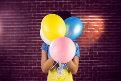 Young woman hiding behind balloons Royalty Free Stock Photography