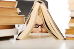 Young woman hiding behind a book Royalty Free Stock Images