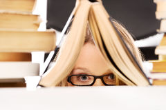 Young woman hiding behind a book Royalty Free Stock Photography