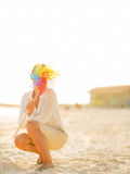 Young woman hiding behind colorful windmill toy Stock Photo