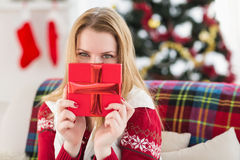 Young woman hiding behind a gift. At home in the living room Stock Photos