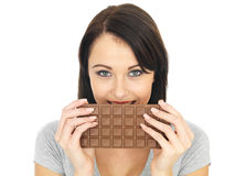 Young Woman Hiding Behind a Milk Chocolate Bar Royalty Free Stock Images