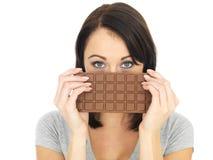Young Woman Hiding Behind a Milk Chocolate Bar Stock Photos
