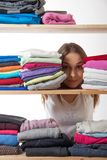 Young woman hiding behind a shelf with clothing Stock Photos