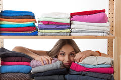 Young woman hiding behind a shelf with clothing Royalty Free Stock Image
