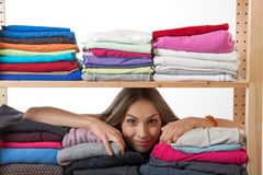 Young woman hiding behind a shelf with clothing Royalty Free Stock Photos
