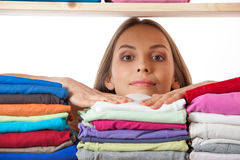 Young woman hiding behind a shelf with clothing Stock Photography