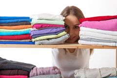Young woman hiding behind a shelf with clothing Stock Photo
