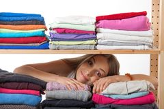 Young woman hiding behind a shelf with clothing Stock Images