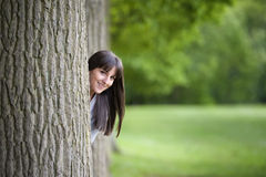 Young woman hiding behind a tree. Beautiful young woman hiding behind a tree Royalty Free Stock Image