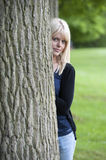 Young woman hiding behind a tree. Beautiful young woman hiding behind a tree Royalty Free Stock Images