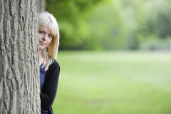 Young woman hiding behind a tree. Beautiful young woman hiding behind a tree Royalty Free Stock Photography