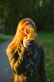 Young woman hiding face behind bunch of leaves Stock Photo