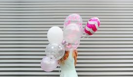 Young woman hiding her face behind pink balloon over striped background Royalty Free Stock Image