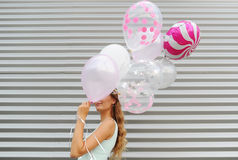 Young woman hiding her face behind pink balloon over striped background Stock Images