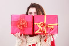 Woman holds red christmas gift boxes. Young woman hiding her face behind presents two gift boxes with ribbon. Christmas season celebration concept Royalty Free Stock Photo