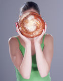 Young woman hiding her face behind a round bun. Royalty Free Stock Photos