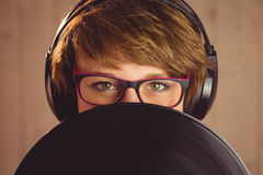 Young woman hiding herself behind vinyl Royalty Free Stock Photos