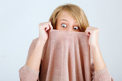 Young woman hiding from the horror in his jacket. Young girl hiding from the horror in his jacket Royalty Free Stock Image