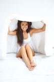 Young woman hiding under the bedclothes Stock Photos