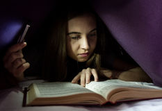 Young woman hiding under blanket and enrapt reading interesting book at nighttime. Girl lighting with the phone as a Royalty Free Stock Image